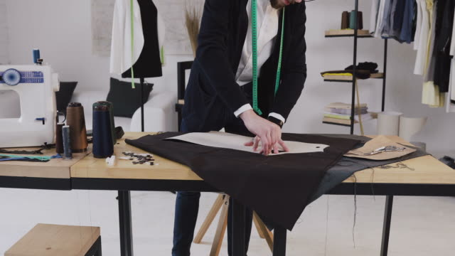Fashion designer or tailor making a pattern on a brown piece of tissue. Dressmaker is using a chalk, holding the sketch on brown textile. Atelier, workplace of seamstress