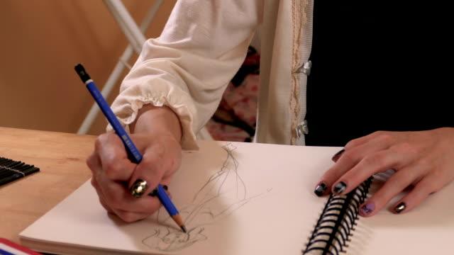 vídeos y material grabado en eventos de stock de diseñador de moda dibujo de estudio, de cerca - bocetos de diseños de moda