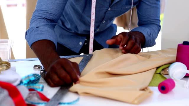 Fashion designer using a ruler on fabric video