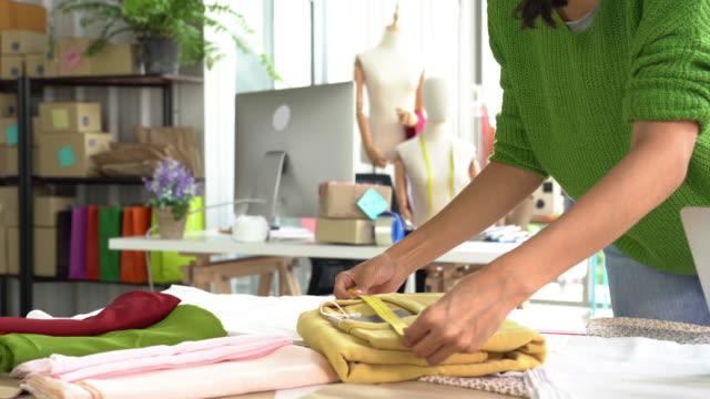 vídeos de stock, filmes e b-roll de desenhador de moda que trabalha no estúdio e no telefone com um cliente - boutique