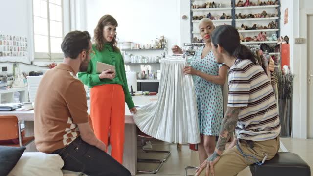 projektanci mody dyskutują o stroju w biurze - 30 39 lat filmów i materiałów b-roll
