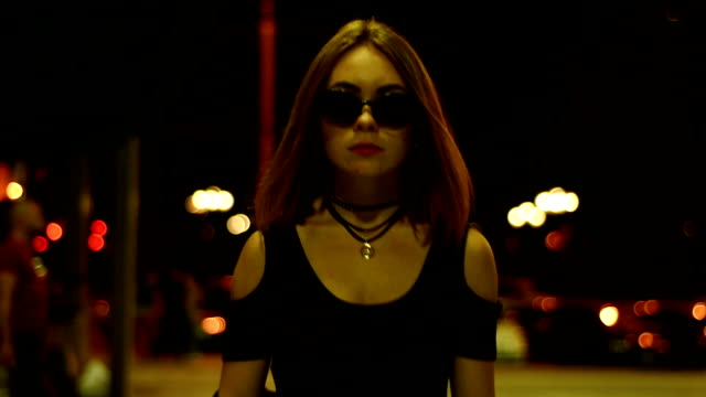 fashion girl in glasses looks into the camera goes the city at night and dress leather jacket