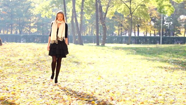 Chica de moda caminando en el parque - vídeo