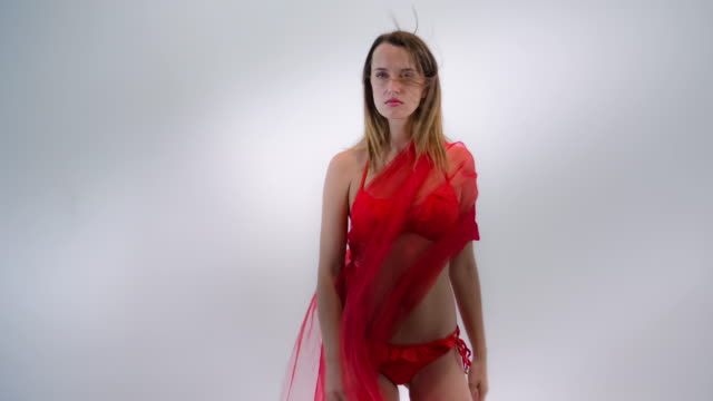 Fashion model in bikini with flowing red fabric video