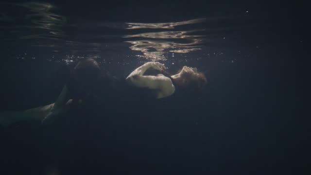 Fashion model in black dress swimming underwater on dark background