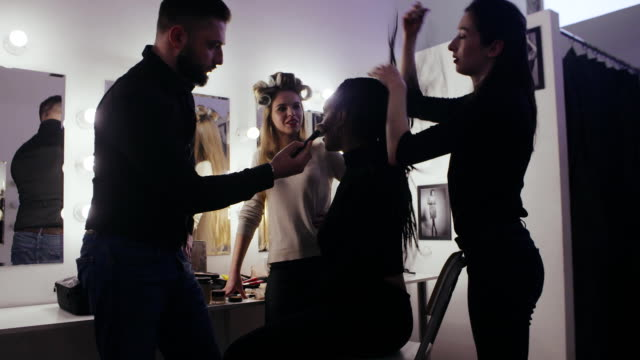 fashion models together professional stylist and makeup artist in dressing room - hairdresser стоковые видео и кадры b-roll