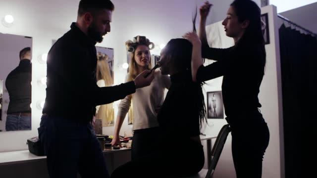 Moda modelos juntos estilista profesional y artista de maquillaje en vestidor - vídeo