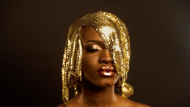 fashion portrait of glossy african american woman with bright golden makeup. bronze bodypaint, black studio background - occhiata laterale video stock e b–roll
