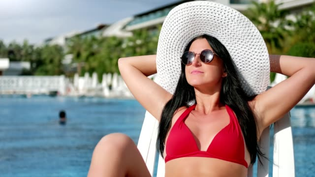 Fashion travel woman in red swimsuit sunbathing on deck chair at luxury hotel medium close-up