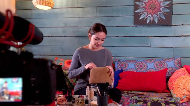 fashion vlogger showing beauty products from make-up bag - kosmetyczka praca w salonie piękności filmów i materiałów b-roll