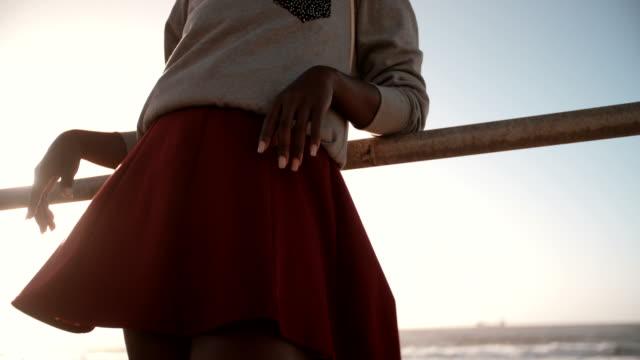 vidéos et rushes de bas de bikini tendance coiffure afro teen fille s'appuyant sur la rampe à la plage - mode de la plage