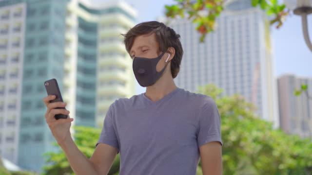 modische schwarze medizinische maske mit einem filter in der stadt. coronavirus 2019-ncov epidemie konzept. mann in schwarzer medizinischer maske spricht mit einem telefon auf einer stadtstraße - wachsamkeit stock-videos und b-roll-filmmaterial