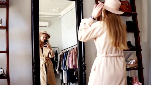 Modische blonde Mädchen vor dem Spiegel in beige Mantel und trendigen Hut stehen, machen ein Foto von Look mit ihrem Smartphone. Genießen Sie ihren Stil. Filmmaterial von der Rückseite. Spiegelreflexionsaufnahme – Video