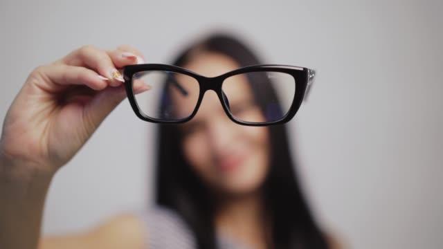 modische brillen hautnah auf dem verschwommenen hintergrund einer frau. - augenoptiker stock-videos und b-roll-filmmaterial