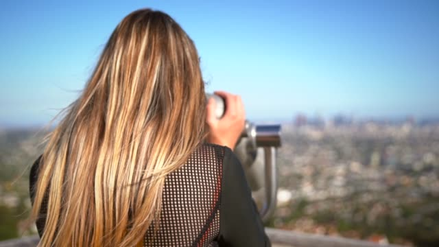fashionable female tourist looking at city skyline through binocular scopes video