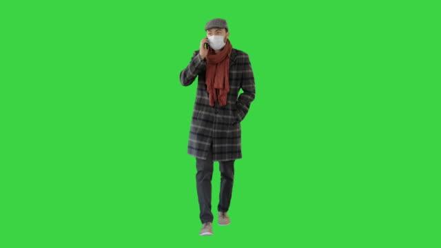 vídeos y material grabado en eventos de stock de caballero de moda en máscara médica llamando al teléfono en una pantalla verde, chroma key - abrigo