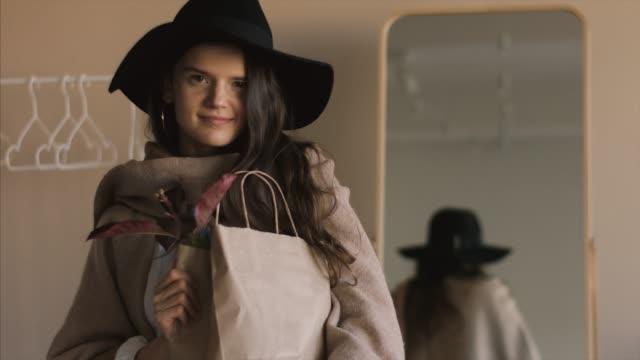 Fille à la mode avec maquette en papier sac posant à l'intérieur - Vidéo