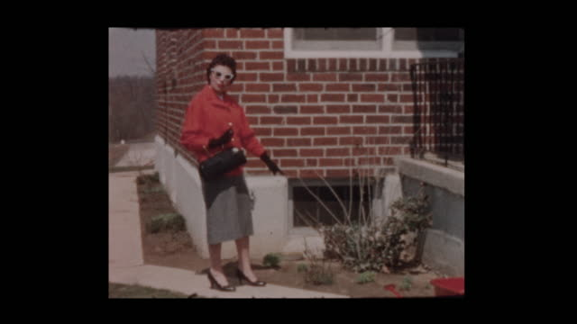 vídeos de stock e filmes b-roll de 1960 fashionable glam 50's mom in sunglasses points to bush - passado