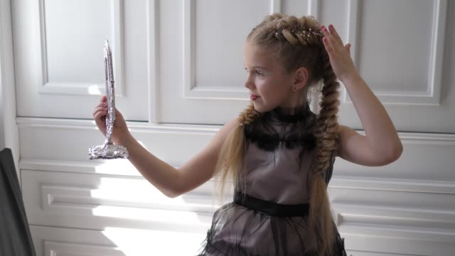 Fashionable Little girl with beautiful hairstyle and Stylish makeup looks in mirror on background white wall Fashionable Little girl with beautiful hairstyle and Stylish makeup looks in mirror indoors on background white wall princess stock videos & royalty-free footage