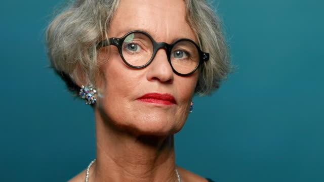 fashionabla mogen kvinna mot blå bakgrund - mature women studio grey hair bildbanksvideor och videomaterial från bakom kulisserna