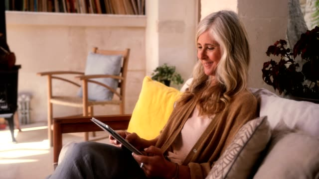 fashionable mature woman having fun using tablet at home - giovane nell'animo video stock e b–roll