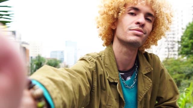 vídeos de stock, filmes e b-roll de homens elegantes com cabelo encaracolado, tomando um selfie - moda masculina