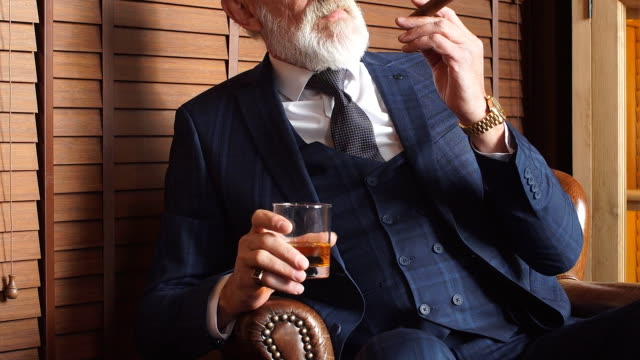 fashionable old man holding a glass of whiskey and going to smoke a cigar - whisky video stock e b–roll
