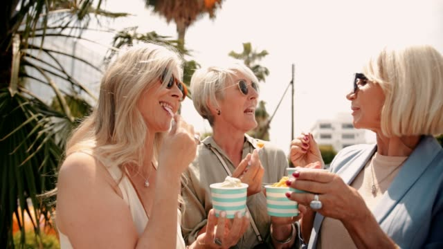 fashionable senior women eating ice cream in the city together - amicizia tra donne video stock e b–roll