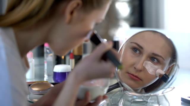 Fashionable woman gently and carefully putting moisturizing mask under eyes video