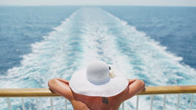 Fashionable woman looking at the ship's wake