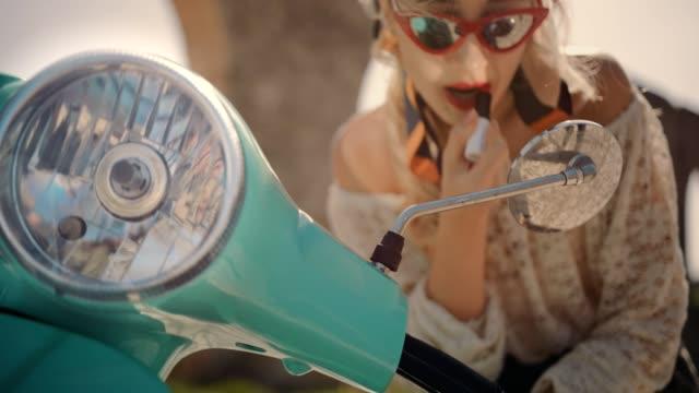 Moda mujer mirando en el espejo de la vespa y la fijación de lápiz labial - vídeo