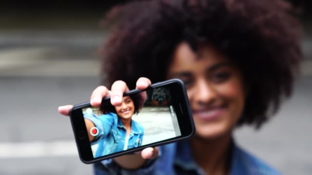fashionable woman taking a selfie with curly hair at street - selfie stock videos & royalty-free footage