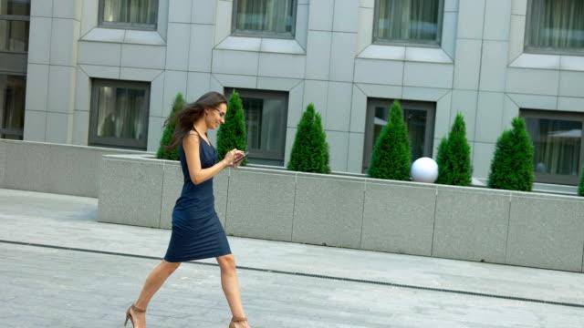 vídeos de stock, filmes e b-roll de mulher elegante, usando o tablet pc andar lá fora. mulher de negócios moderna vestindo óculos e roupas elegantes - saia