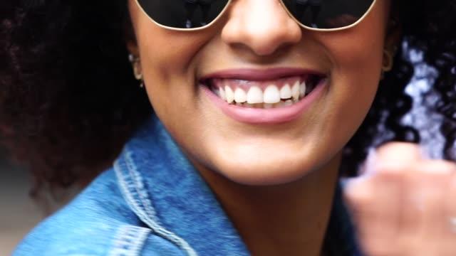 modische frau mit lockigem haar auf straße - sonnenbrille stock-videos und b-roll-filmmaterial