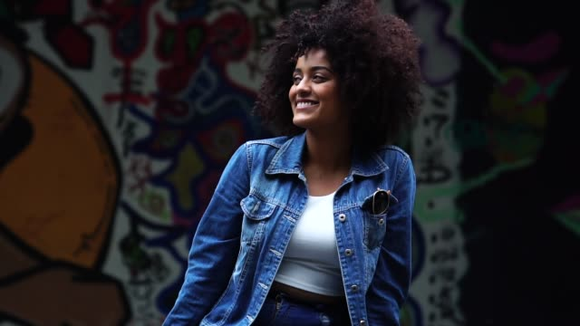 vídeos de stock e filmes b-roll de fashionable woman with curly hair at street - afro