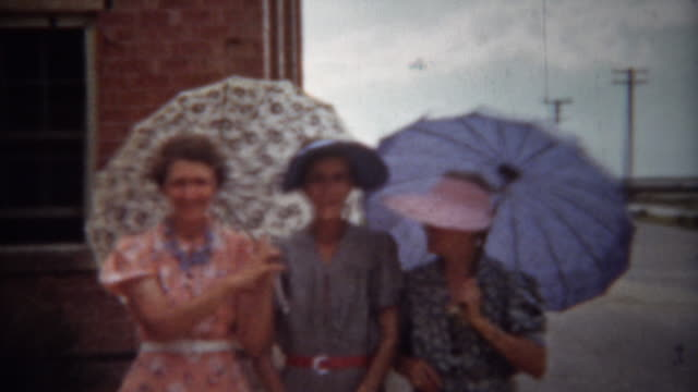 1940: Fashionable women with sun umbrellas and colorful dresses. video