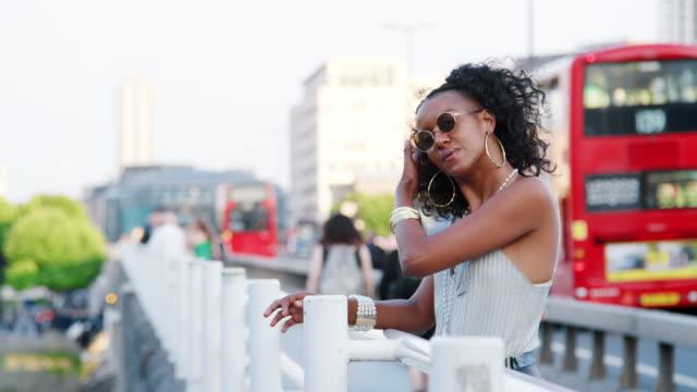Modisch junge schwarze Frau stützte sich auf das Geländer einer Brücke in der Stadt umzusehen, Seitenansicht – Video