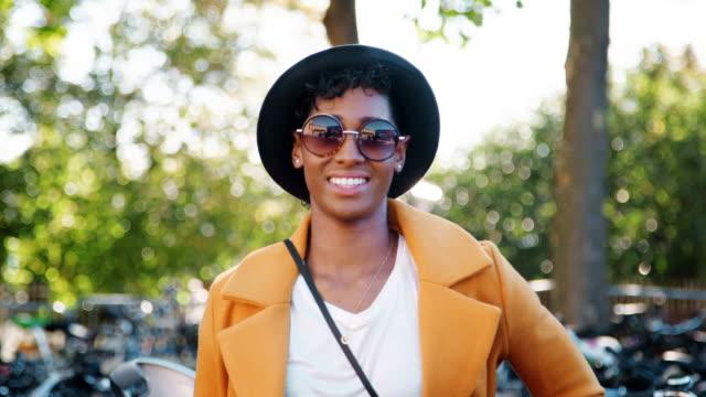 vídeos y material grabado en eventos de stock de moda joven mujer negro permanente al aire libre llevando gafas de sol, una capa amarilla y un sombrero negro mirando a la cámara y riendo, cierre para arriba, centrarse en primer plano - moda playera