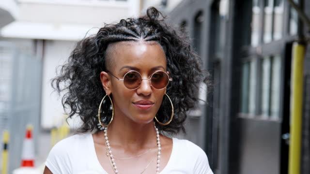 vidéos et rushes de à la mode jeune femme noire tournant et donnant à la caméra sur ses lunettes de soleil rondes et riant, gros plan - mode londres