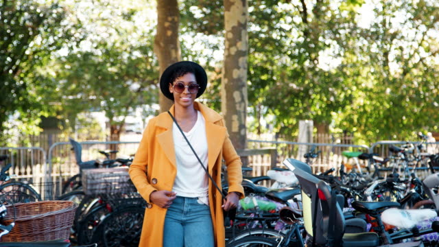 stockvideo's en b-roll-footage met modieuze jonge zwarte vrouw die het dragen van een hoed, zonnebril, blue jeans, een unbuttoned gele erwt jas en een crossbody handtas onder geparkeerde fietsen, wandelen lacht naar camera - street style