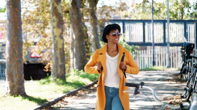 vídeos de stock, filmes e b-roll de na moda jovem negra com um chapéu, óculos de sol, azul jeans e um casaco de ervilha amarelo andando ao longo de uma rua em um dia ensolarado, olhando ao redor, sorrindo, vista frontal da cidade atravês - camiseta preta