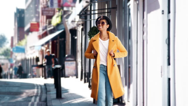 Fashionable young black woman wearing blue jeans and an unbuttoned yellow pea coat walking on pavement near shops on a sunny day smiling, close up