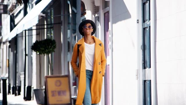 vídeos y material grabado en eventos de stock de moda joven negro vistiendo jeans de mujer y una capa de guisante amarillo desabrochada caminando en la calle pasado de tiendas en un día soleado, sonriente, cerca - moda playera