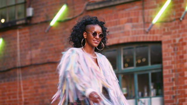 Fashionable young black woman wearing multicoloured fringed jacket, sunglasses and jeans turning around laughing, low angle Fashionable young black woman wearing multicoloured fringed jacket, sunglasses and jeans turning around laughing, low angle urban fashion stock videos & royalty-free footage