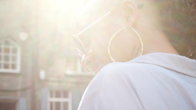 stockvideo's en b-roll-footage met dragen zonnebril trendy jonge zwarte vrouw praten over de straat, close-up, zijaanzicht, lens flare - street style