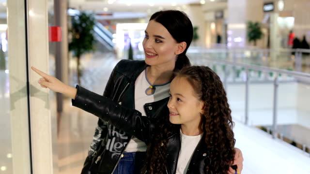 vídeos y material grabado en eventos de stock de chica joven de moda con hermana menor caminando en el centro comercial y de compras. - madre e hijos