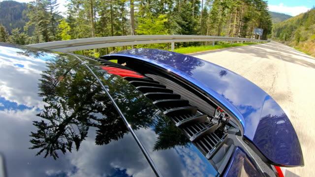 fast car drive on an empty winding road with aerodynamic help from spoiler - spoiler filmów i materiałów b-roll