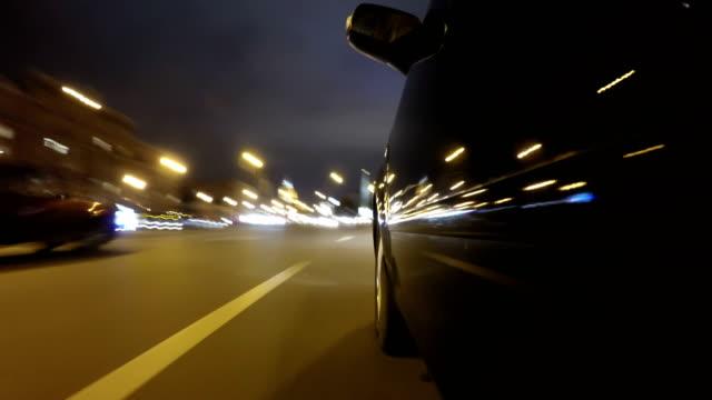 Rápido en coche noche camino de ciudad POV por ciudad en el lado izquierdo del timelapse noche del coche. Vista de ángulo bajo - vídeo
