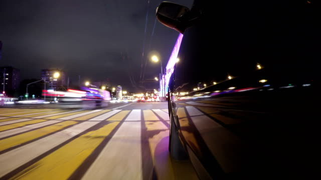 Fast city drive night road POV through city at night timelapse left side of car. Low angle view video