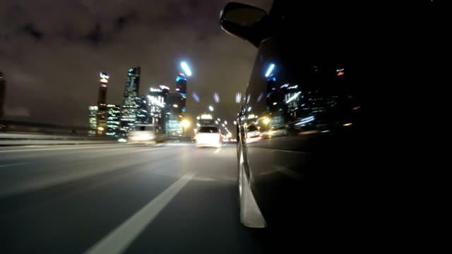 Route ville rapide lecteur nuit POV par la ville de nuit timelapse côté gauche de la voiture. Faible angle vue - Vidéo